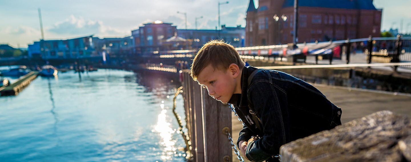 A child pondering over the River